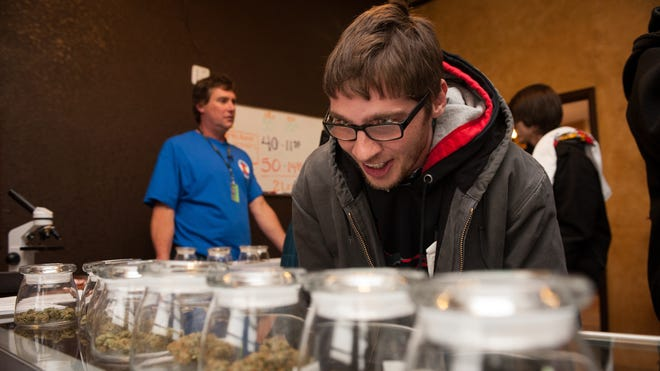 Tyler Williams of Blanchester, Ohio, selects marijuana to purchase at the 3-D Denver Discrete Dispensary on Jan. 1.