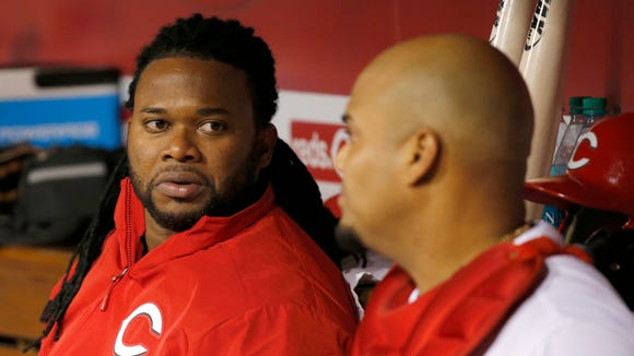 Reds starting pitcher Johnny Cueto (left) talks to catcher Brayan Pena in the dugout.