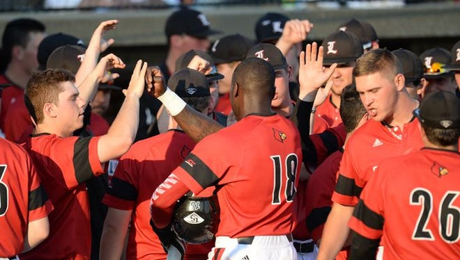 U of L outfielder Mike White is greeted after scoring the first run of the University of Louisville vs. University of Kentucky baseball game at Cliff Hagan Stadium in Lexington.