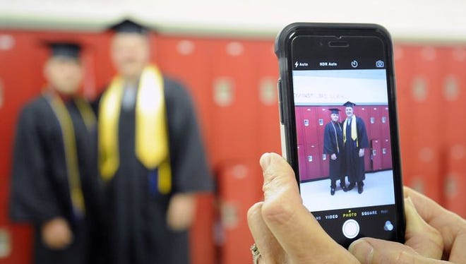 Two graduating seniors pose for a cellphone photo prior to ceremonies at Norfork High School on Friday night.