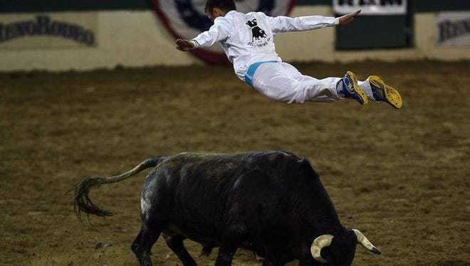 French Bull jumper Emmanuel Lataste leaps over a charging bull during the 2015 Reno Rodeo