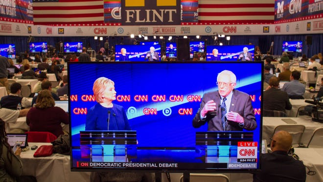 Journalists March 6, 2016, watch Democratic presidential candidates Hillary Clinton and Bernie Sanders debate on televisions in the media room at the University of Michigan in Flint, Mich.