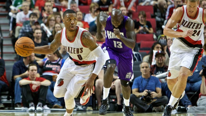 Portland Trail Blazers guard Damian Lillard, left, leads a fast break past Sacramento Kings forward Quincy Acy, center, during the second half of an NBA basketball preseason game in Portland, Ore., Monday, Oct. 5, 2015.