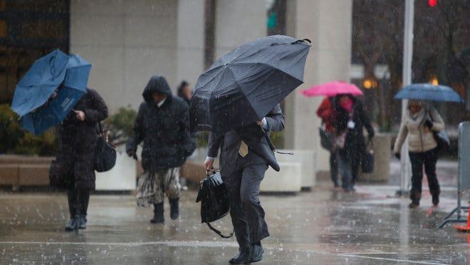 Pedestrians walk in the rain in downtown White Plains on Dec. 9, 2014.