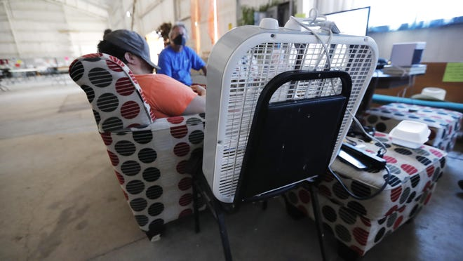 Grace Campus homeless residents sit in the barn next to a fan trying to stay cool during a heat wave in July, Friday July 10, 2020.