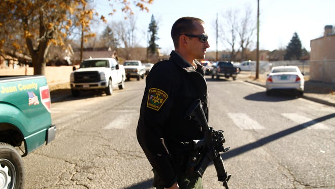 A San Juan County Sheriff's deputy stood watch near the entrance of Aztec High School on Thursday, Dec. 7, 2017, the day of the deadly shootings there.