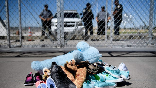 Security personal stand before shoes and toys left at the Tornillo Port of Entry where minors crossing the border without proper papers have been housed after being separated from adults, June 21, 2018 in Tornillo, Texas.