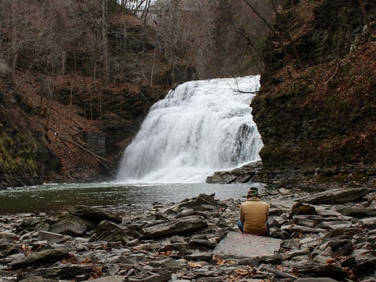 Cornell alum Nathaniel Young sits below Forest Falls in an area only accessible via Ezra's Tunnel.
