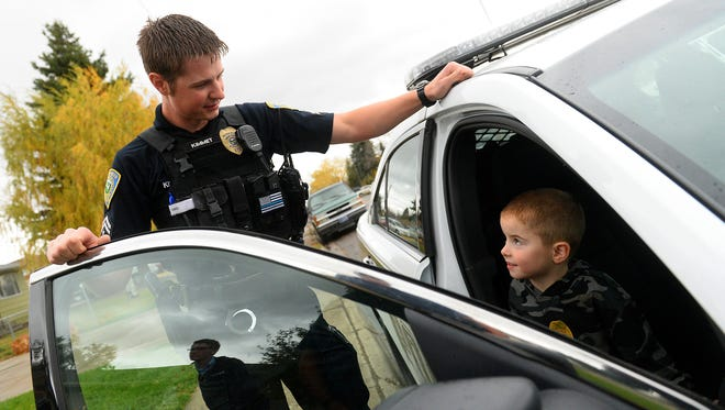 Officer Tad Kimmet of the Great Falls Police Department gives Bentley Liston, 5, a tour of a GFPD patrol car during the Coffee with a Cop community event at Schulte's Coffee House on Tuesday morning.