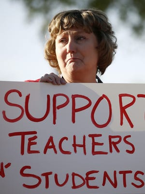 "Nanette Swanson, a teacher at Tuscano Elementary School, begins to cry as she joins other teachers, parents and students as they stage a ""walk-in"" for higher pay and school funding on April 11, 2018, in Phoenix. Teachers gathered outside Arizona schools to show solidarity in their demand for higher salaries staging ""walk-ins"" at approximately 1,000 schools that are part of a statewide campaign for a 20 percent raise and more than $1 billion in new education funding."