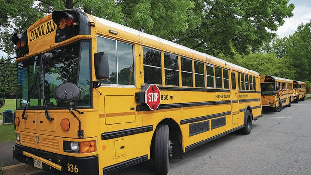 Fairfax County Public School buses parked at a middle school in Falls Church, Va., Monday, July 20, 2020. Very few Americans believe schools should return to normal operations this fall, a new poll says. J. Scott Applewhite/AP