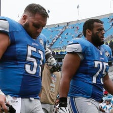 Dejected Lions Dominic Raiola, left, and Larry Warford walk off the field after Sunday's 24-7 loss to the Panthers in Carolina.
