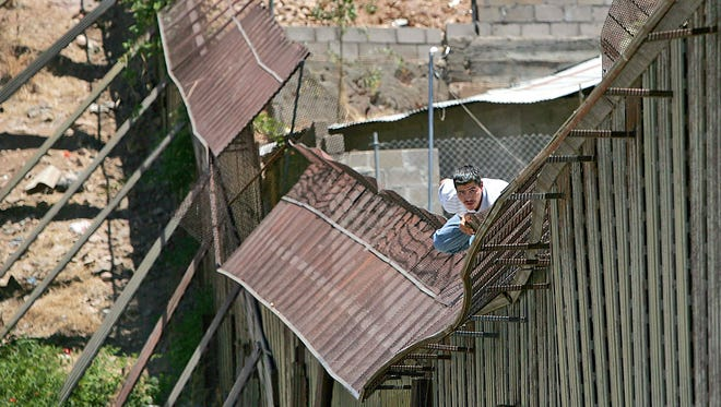 In this May 31, 2006, photo, a man climbs over the international border into Nogales, Ariz., from Nogales, Mexico. Presumptive GOP nominee Donald Trump's push for a border wall is not a new idea, and since World War I, has been pursued often. Historians said opponents of Mexican immigration have advocated for a wall off and on for about 100 years with little results due to changing technologies and pressure to divert enforcement attention elsewhere.