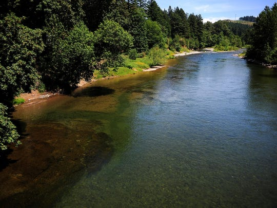The Santiam River flows as seen from the Albany-Lyons Highway bridge, on Monday, June 22, 2015, in Mehama, Ore. Afternoon fishing will be closed down on many Oregon rivers beginning Saturday, and will be closed entirely on some streams due to the ongoing drought and high water temperatures.