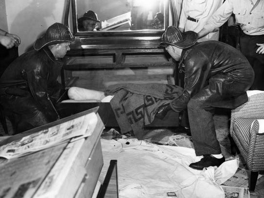 Members of the Indianapolis fire department rescue squad remove the body of Dorothy Poore from the dresser drawer in room 665 of the Claypool Hotel, July 18, 1954. The upper part of the body is covered in a blanket.
