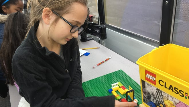 Blue Ash Elementary School third-grader Annabelle Daft prepares to launch a marble through a Lego maze she built. This is among a variety of activities offered on a school bus retrofitted for use as a science and math classroom. Dec. 5, 2017