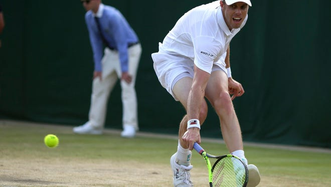 Thousand Oaks High graduate Sam Querrey reaches low to return a shot by Jo-Wilfried Tsonga during their third-round match at Wimbledon on Saturday. The match was suspended because of darkness, with Querrey leading 6-5 in the fifth set.