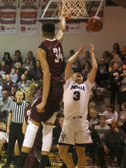Oskaloosa freshman Xavier Foster blocks a shot by Norwalk
