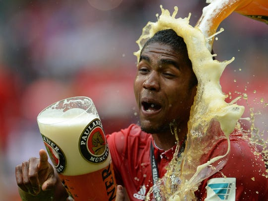 Munich's Douglas Costa is  is sprayed with beer  during celebrations of  Bayern Munich's German soccer championships in Munich, Germany, Saturday May 14, 2016.