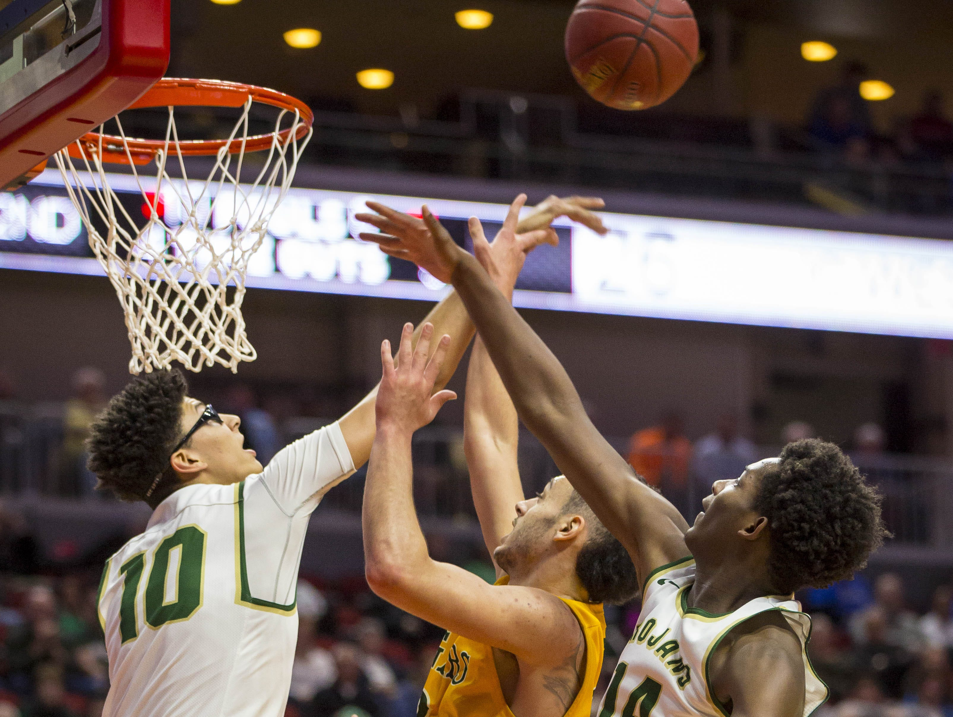 Iowa City West High's Seybian Sims (10) and Hakeem Odunsi block a shot by Cedar Rapids Kennedy's Drake Brewster during their Class 4A semifinal at the Iowa boys' high school basketball tournament Friday at Wells Fargo Arena in Des Moines.