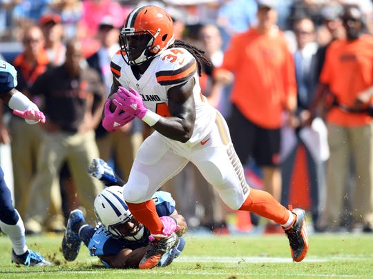 Cleveland Browns running back Isaiah Crowell (34) runs past a tackle attempt by Tennessee Titans linebacker Avery Williamson (54) in the first half at Nissan Stadium.