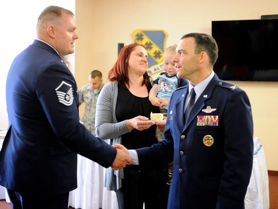 Retired Master Sgt. Kristopher Parker (left) get congratulations
