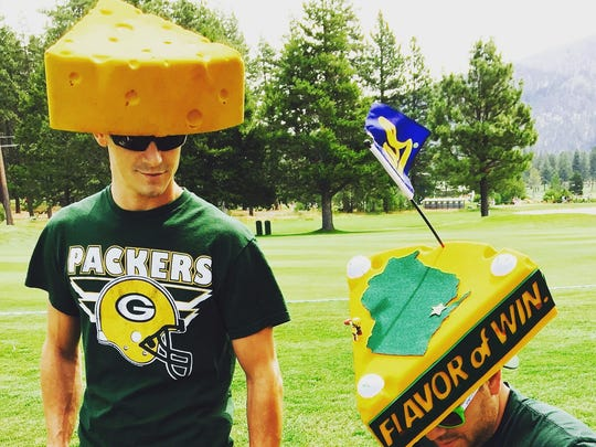 Neal Dubisky, right, shows off his customized Winner Green gum Cheesehead, complete with a tiny Aaron Rodgers figurine made of LEGOs.