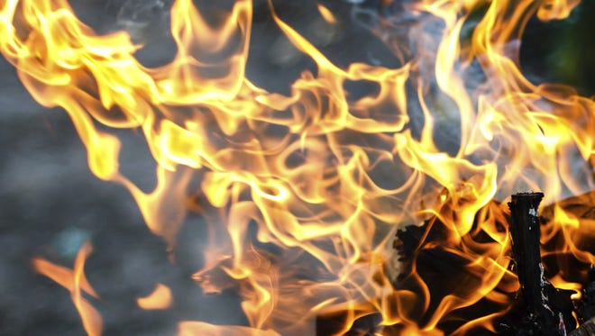 A file photo of flames over burning wood in brazier.