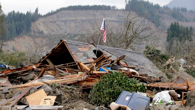 A flag sticks out of a hole in a demolished home near where a deadly mudslide from the hill behind that happened several days earlier ended, Tuesday, March 25, 2014, in Arlington, Wash.