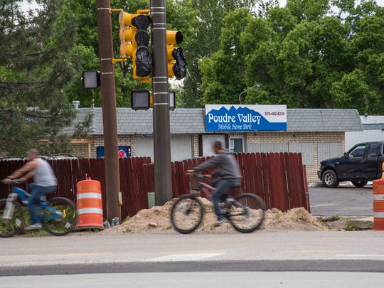 Two bicyclists leave the grounds of Poudre Valley Mobile