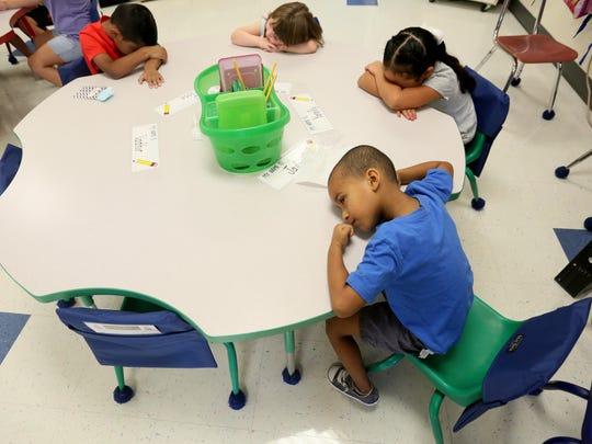 5 year-old Jorge Alvarez rest his head on his desk alongside his new kindergarten classmates at Marbrook Elementary School.