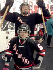 John Tebay, 19, of Hellam Township raises his hands above Emily Leiphart, 20, of Chanceford Township (seated). Their families drive them more than an hour each way to play for the Palmyra Black Knights sled hockey team -- one of only four hockey teams for disabled youth and adults in Pennsylvania.