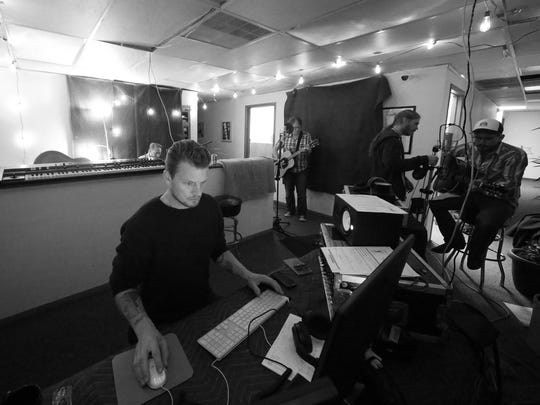 """Marcus Amundsen Trana works at the soundboard with musicians Ryan Thompson, Jimm McIver, Steve Smith and John Hvezda, from left behnd Trana, as they record a track for """"Dark Songs."""" An album of songs created and recorded at the previous year's songwriting event is released each year at the """"Dark Songs"""" concerts."""