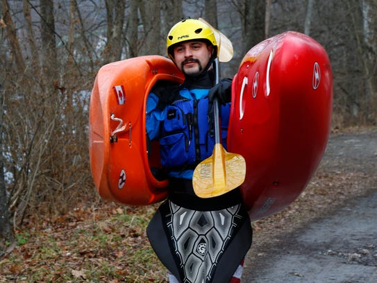 Adam Holton carries his kayaks to a launching point along the Chenango River in Chenango Forks on Monday, December 4, 2017.