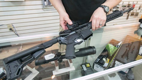 Jason Brenden adds a scope to an AR-15 rifle at Caswells in Mesa in 2013.