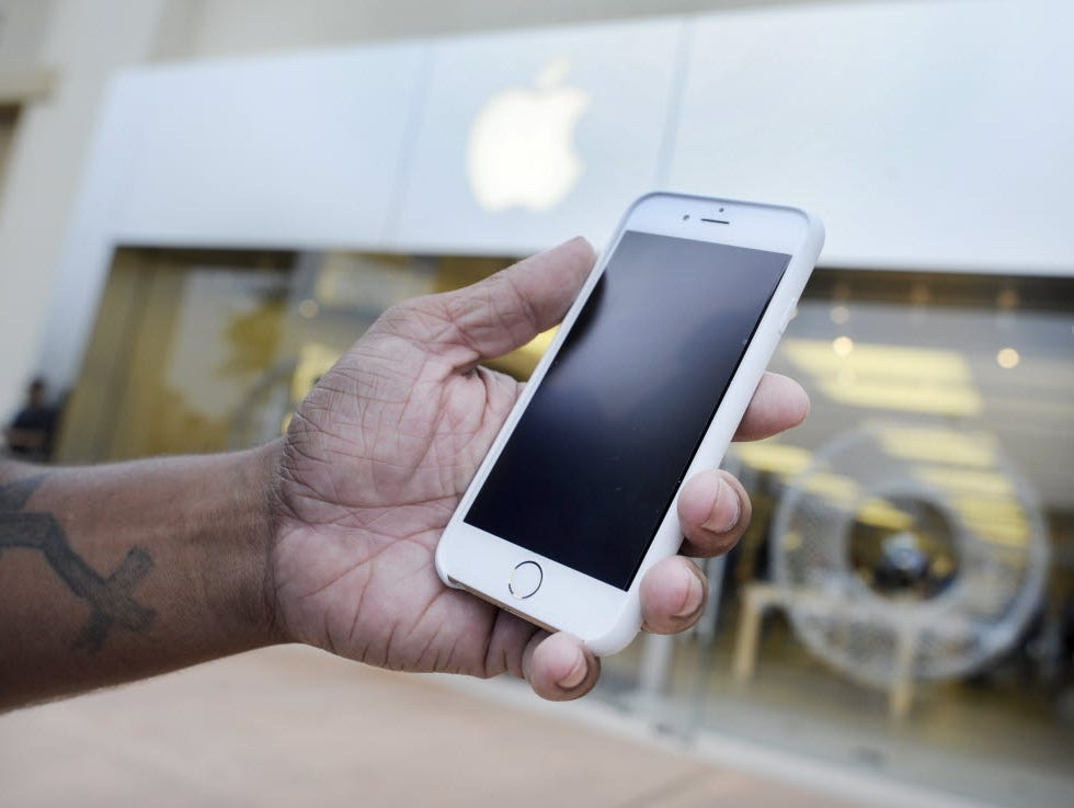 Josh Nolan holds his new iPhone 6 at an Apple Store in Augusta, Ga., in October 2014.