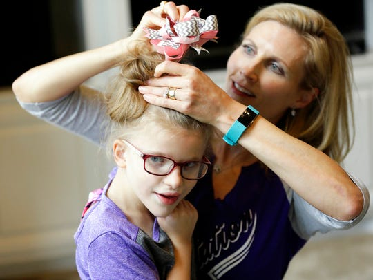 """Stacey English, right, fixes the hair of her 7-year-old daughter, Addison, in Houston on Friday, June 23, 2017. Stacey said her former therapist, who went out of business, introduced Addison to basic life skills and even new foods """"like smashing up crackers into a little bit of peanut butter."""" (AP Photo/David J. Phillip)"""