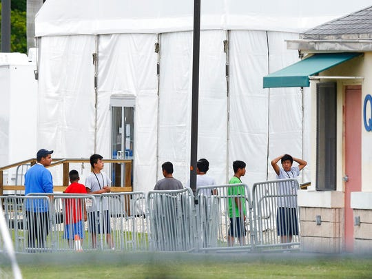Immigrant children walk in a line outside the Homestead