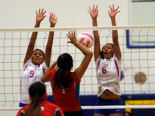 Bloomfield's Taneesha Valdez, left, and Shaylee Charley, right, defend the net as Shiprock's Chamika Begaye prepares to spike the ball on Tuesday at Bobcat Gym in Bloomfield.