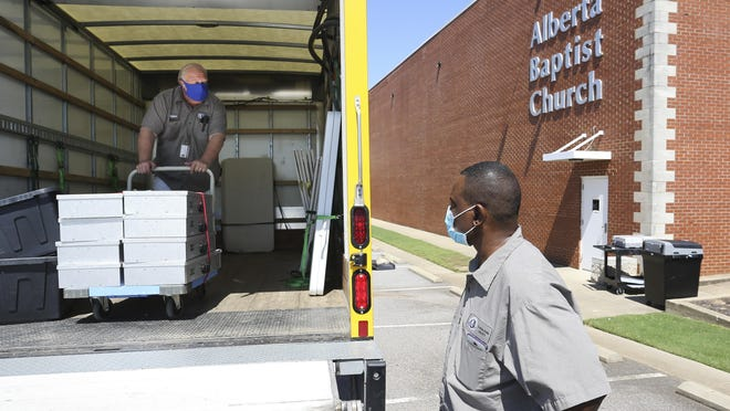 Anthony Beck and Arthur Richardson unload voting equipment at Alberta Baptist Church in preparation for the runoff election Monday, July 13, 2020. Polls will be open from 7 a.m. until 7 p.m. Tuesday.