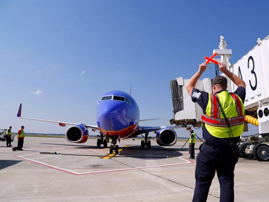 Des Moines International Airport ground crewman Josh Butler, right, signals as a Southwest Airlines flight arrives to the gate in September 2013.