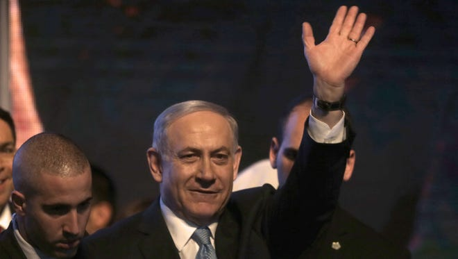 Israeli Prime Minister Benjamin Netanyahu waves to  supporters as reacts to exit poll figures.