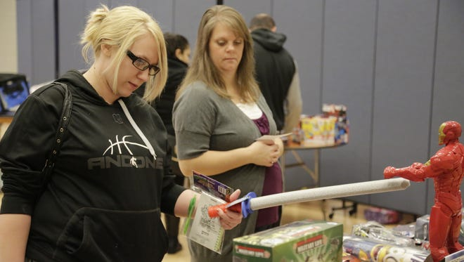 Morgan Walker, 23, of West Lafayette shops for toys Saturday, Dec. 12, 2015, at Faith Community Center in Lafayette as part of Christmas for Everyone. The program provides toys to local low-income children.