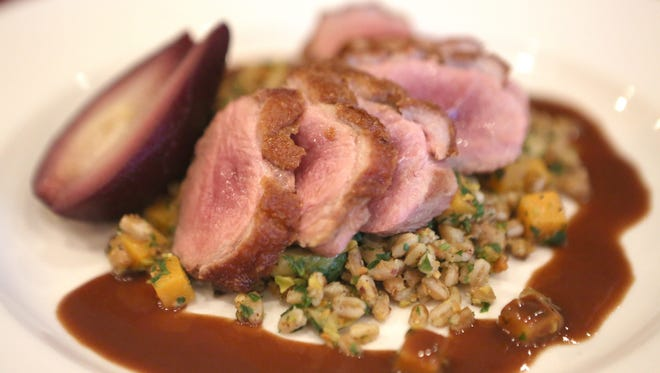 Pan roasted duck breast  from Anea Bistro, in Montgomery. The entree consists of farro, pistachio, poached pear, butternut squash and red wine duck sauce.