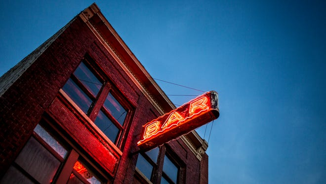 A neon light illuminates in front of the Brass Rail in downtown Port Huron. The city of Port Huron has 29 active on-premises liquor licenses.