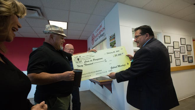 Gabriel Mendoza, center, and Lorenzo Alba Jr., the executive director of Casa de Peregrinos, hold an over-sized check representing the $30,000 that Mendoza and his wife Andrea Mendoza, owners of The Shed restaurant donated to the food bank on Friday, Feb. 23, 2018.