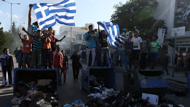 Roma hold Greek flags as they block an avenue during a protest in Athens Sept. 30.  The Greek Roma community, protesting authorities' plans to demolish their illegal settlement and move them to a remote spot in the countryside, blocked a main northern Athens avenue for hours .