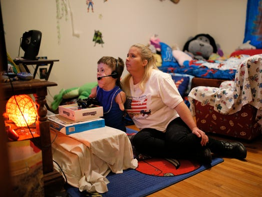Michaela Mitchell watches her son Jeremiah, 10, play Xbox in his bedroom in Tulsa. Mitchell is teaching Jeremiah how to live again after meningitis contracted from an outbreak at his school forced doctors to amputate both his arms and legs.