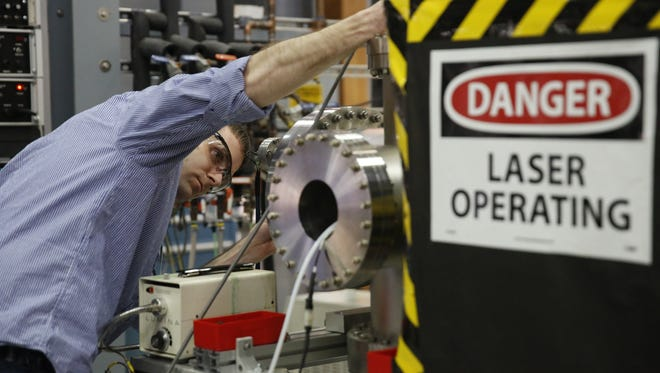 Staff scientist Paul Dunk fine-tunes a laser he's using to synthesize carbon nano-cages as part of his research at the National High Magnetic Field Laboratory Tuesday.