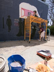 Artist Liz Rowse of Howell, on the scaffold, paints